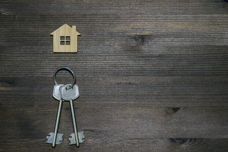 Symbol of a bamboo house with a metal keys on a brown vintage wooden background. Lighting gradient. The concept of selling real estate with the transfer of ownership.