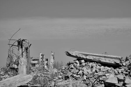 The remains of a destroyed building with concrete Foundation piles sticking out of the ground. Black and white background