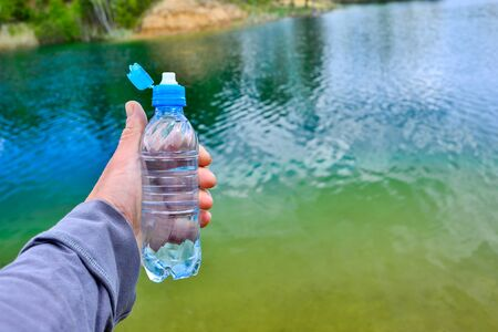 A mans hand holds a water bottle close-up against the background of clear water of a lake with a turquoise hue with the shore in the distance. Imagens