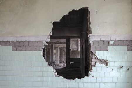 A hole in the wall of a large tiled building. Background.
