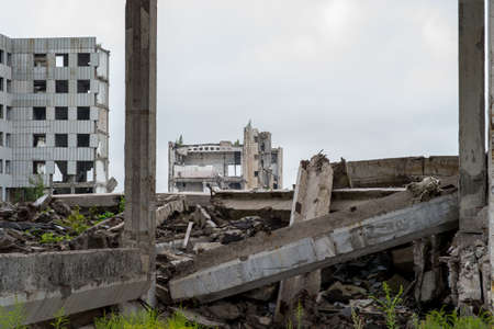 A large destroyed building with a pile of gray concrete debris and beams in the foreground. Background. 写真素材