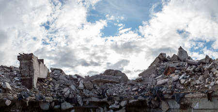 A pile of concrete gray debris of a destroyed building with a huge beam in the foreground against a blue sky with clouds.