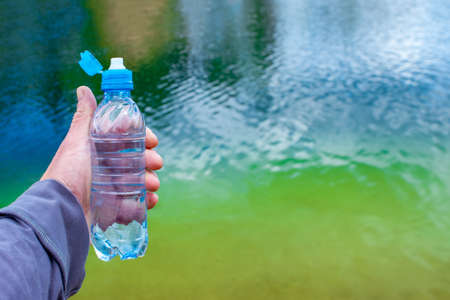 A blue plastic bottle in a mans hand on the background of turquoise lake water. Background. Imagens