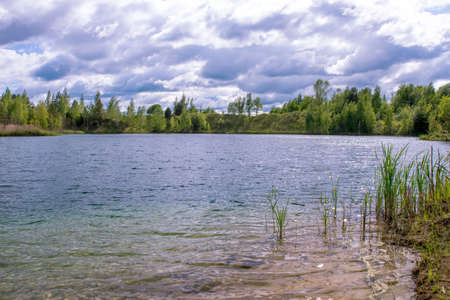 Lake with clear blue water of turquoise hue with banks in bright spring green against the sky with Cumulus clouds.