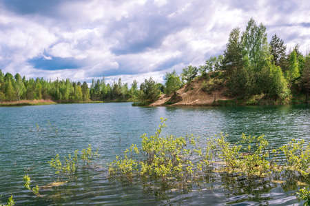 Lake with blue water and turquoise hue with banks in bright spring green against the sky with Cumulus clouds.