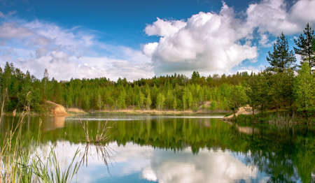 Lake with banks in bright spring green mixed forest with reflection of blue sky with clouds in clear water.
