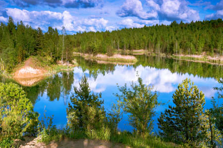 Beautiful forest lake with blue water and banks with mixed forest on the background of the sky with blue-gray clouds.