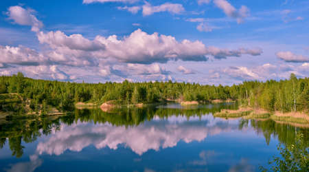 Lake with banks in the bright spring green of the forest with a reflection of the blue sky with clouds in clear water.