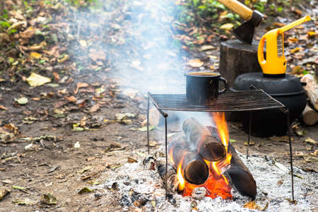 Metal black sooty mug on the grill on an open fire on the against the background of Hiking gear and autumn leaves.