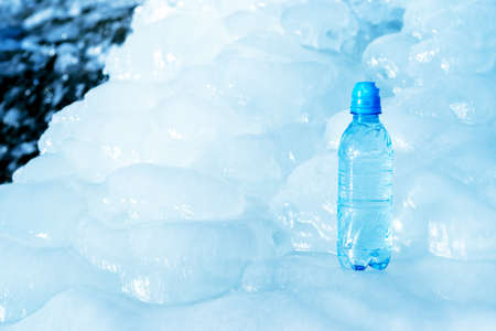 Blue plastic bottle on ice against the background of the glacier meltwater flow. Background.