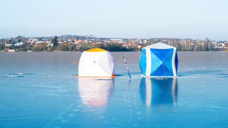 Two tents of fishermen on blue ice on a clear frosty day against the background of a cottage village.