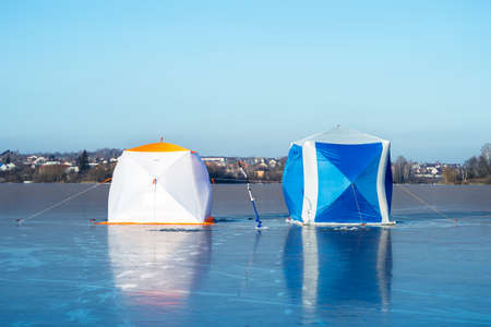 Two fishermens tents close-up on blue ice on a clear frosty morning against the background of a cottage village.