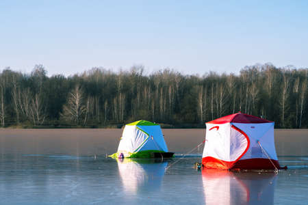 Two fishermens tents close-up on blue ice on a clear frosty day against the background of a winter forest.