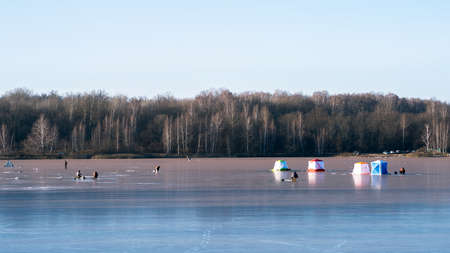 Tents and fishermen ice fishing on the blue ice of the lake on a clear frosty morning against the background of a winter forest.