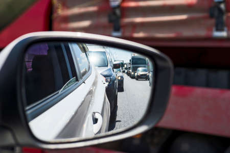 Car rear view mirror with reflection of the traffic flow in the tube. Concept: modern rhythm of life 版權商用圖片
