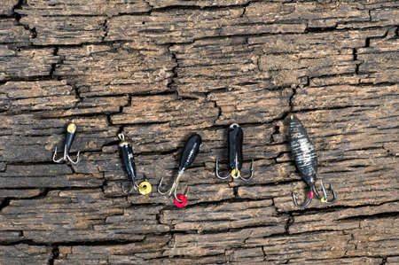 Set of lures for ice fishing shot from above on a cracked wooden background 版權商用圖片
