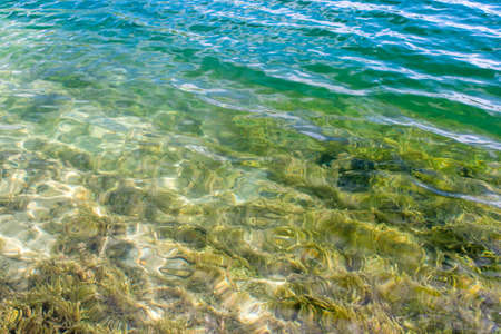 Clear clear water of the lake with a turquoise hue on a sandy beach. The natural background