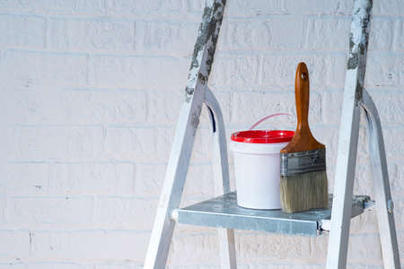 A paintbrush and bucket with a red lid stand on a metal stepladder against a white wall decorated with bricks. 版權商用圖片