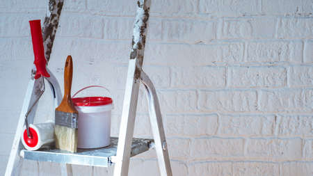 A brush, bucket and textured roller under a brick stand on a metal stepladder near a white wall decorated with bricks.