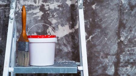 A paintbrush and a bucket of paint stand on a metal stepladder against an untreated concrete wall with remnants of white paint. Background