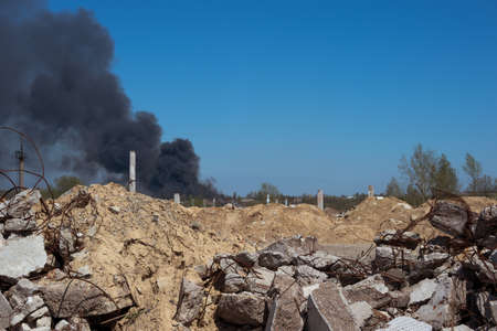 The concrete rubble of the building with bricks and protruding fittings on a background of blue sky with thick black smoke. Background