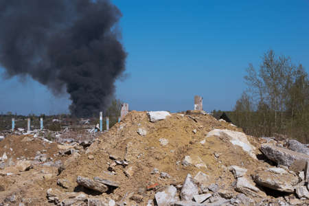 The concrete remains of a ruined building with protruding stilts against a background of black smoke against a blue sky. Background
