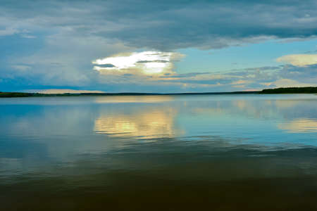 A calm evening sky landscape of pastel colors with a reflection in the smooth waves of a large lake. Natural background 版權商用圖片