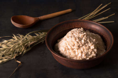 Oatmeal porridge in a vintage clay bowl with ears of oats on a dark table background.