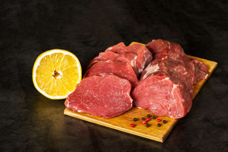 Fresh raw veal tenderloin meat in large chunks and sliced medallions on a wooden chopping board on a dark background.