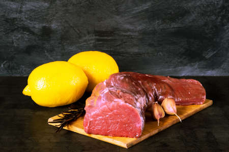 Fresh raw veal tenderloin in a large piece with lemons, sprig of rosemary and garlic on a dark vintage background.