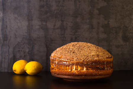 Lemon cake sprinkled with grated chocolate with lemons on a dark vintage background. The concept of making dessert