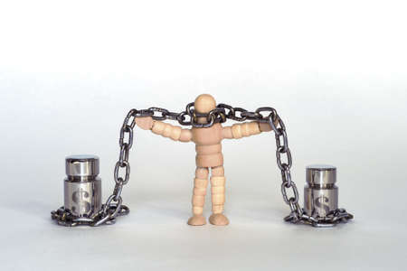 A figure of a man made of wood in chains tied to metal weights with the symbol of the dollar.
