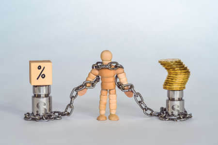 Figure of a man made of wood in chains tied to metal weights with the symbol of the dollar with coins and interest.