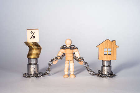 Figure of a man made of wood in chains tied to metal weights with the symbol of the dollar with an imitation of the house, interest with yellow coins.