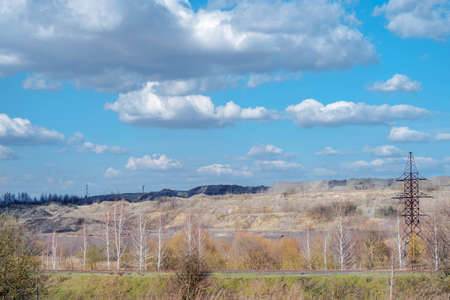 A deserted industrial landscape of rock dumps with remnants of forest, vegetation against the background of a spring sky with white clouds.
