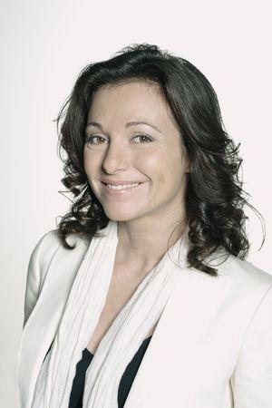 ritratto su sfondo bianco di una donna di quarant'anni in studio sorridente che indossa un giubbotto bianco Archivio Fotografico