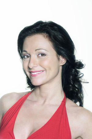 Porträt auf weißem Hintergrund einer vierzig Jahre alten Frau im Studio lächelnd in einem roten Kleid