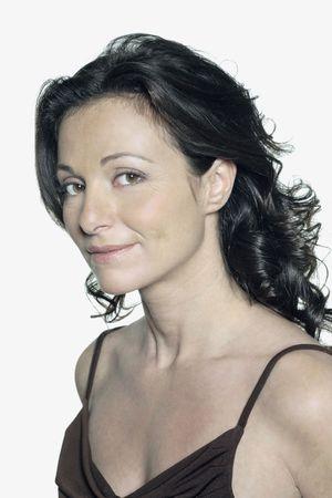 Portrait sur fond blanc d'une femme de quarante ans en studio souriant vêtue d'une robe marron