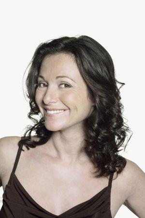 Porträt auf weißem Hintergrund einer vierzig Jahre alten Frau im Studio lächelnd in einem braunen Kleid