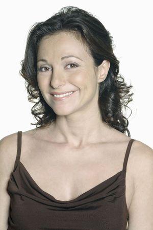 Porträt auf weißem Hintergrund einer vierzig Jahre alten Frau im Studio lächelnd in einem braunen Kleid Standard-Bild