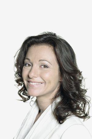 Portrait sur fond blanc d'une femme de quarante ans en studio souriant portant un gilet blanc