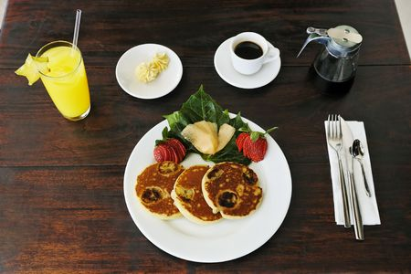 continental breakfast composed of pancakes on a plate with coffee maple syrup and orange fruit juice on a wood made table Foto de archivo - 121743216