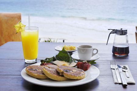 Desayuno continental compuesto de panqueques en un plato con jarabe de arce de café y jugo de naranja sobre una mesa de madera con la playa y el mar al fondo Foto de archivo