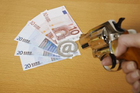 gun pointing euro bills with the arobase e-mail sign on a table 스톡 콘텐츠