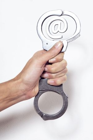 hand holding a handcuffs surrending a arobase e-mail sign Standard-Bild