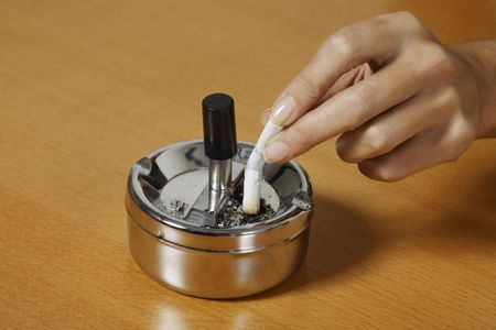 hand crushing a cigarette on an ash tray on a table