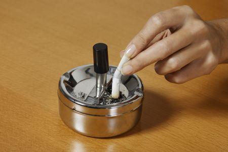 Hand zerquetscht eine Zigarette auf einem Aschenbecher auf einem Tisch Standard-Bild
