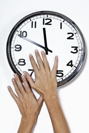 hands trying to stop the advance of the time by grabbing needle of a clock Standard-Bild