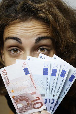 portrait of a women hiding behind euro bills Stock Photo