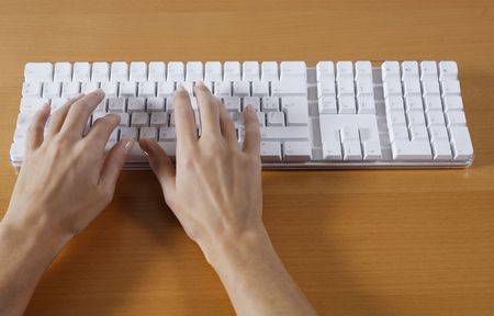 hand typing on a wireless white keyboard computer posed on atable Imagens - 121743394